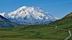 Alaskan mountain towering over green meadow