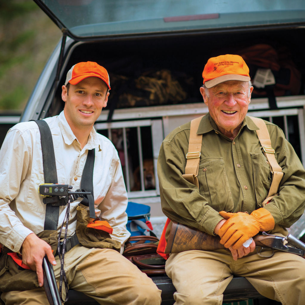 Leigh and his son, Simon, sitting on the back of a truck getting ready to hunt