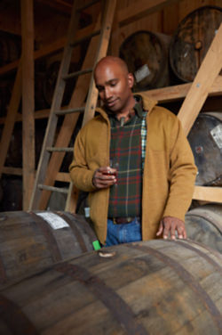 Man holding a glass of whiskey in front of large wooden barrels