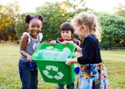 children laughing while holding a recycling bin