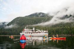 People in kayaks on calm water in Alaska