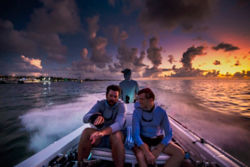 three people in a speeding boat at sunset