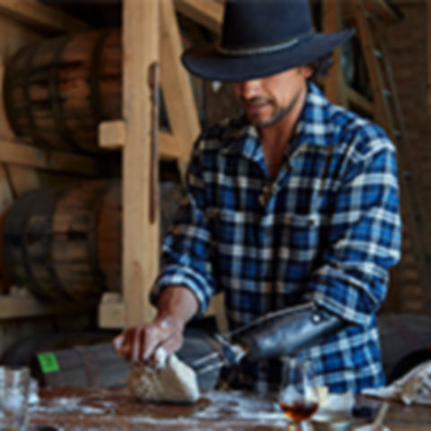 Man with hat wearing a flannel kneading dough.