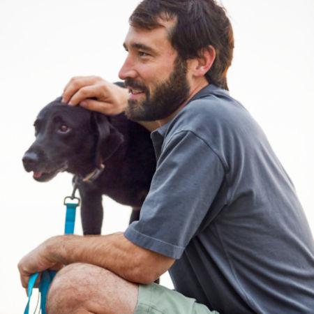 A bearded man in a blue polo shirt sitting with a black Labrador Retriever