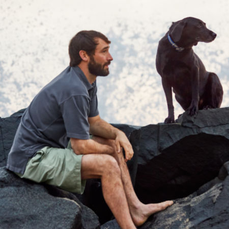 Charlie Perkins and his dog Romi sitting on black rocks with the splash of a wave in the background.