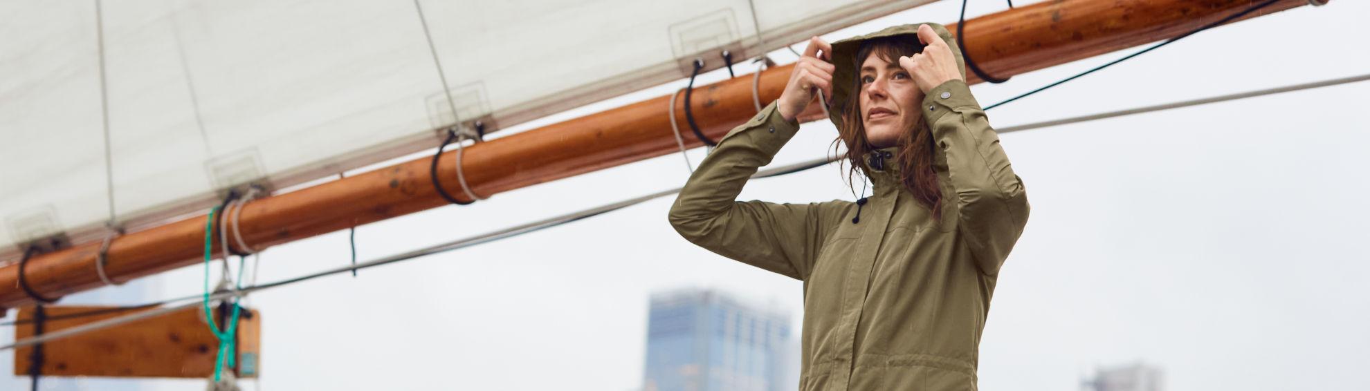 Woman wearing raincoat on a. sailboat