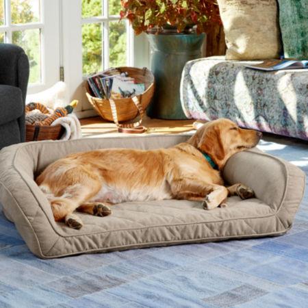 A Golden Retriever sleeping on an Orvis dog bed