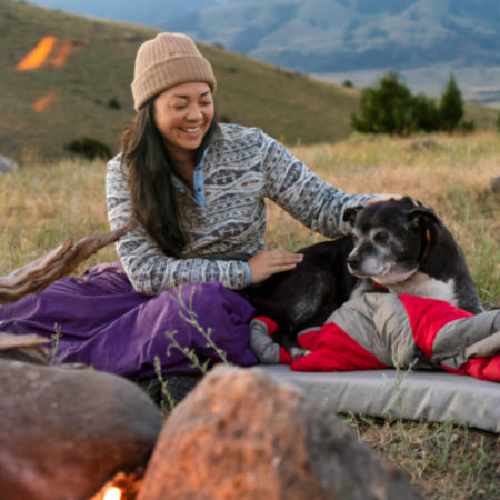 Woman Pets her dog near a campfire