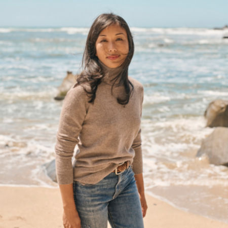A woman standing in front of the ocean wearing jeans and a tan cashmere sweater