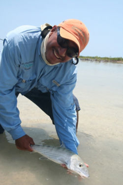 man standing in water holding a bonefish
