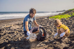 Dad and son cleaning up the beach. Natural education of children