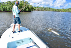 man standing on boat reeling in large fish