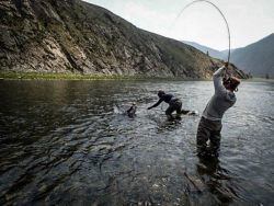 two people in river reeling in a fish