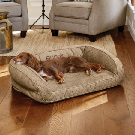 Dog laying on an Orvis brown tweed bolster bed
