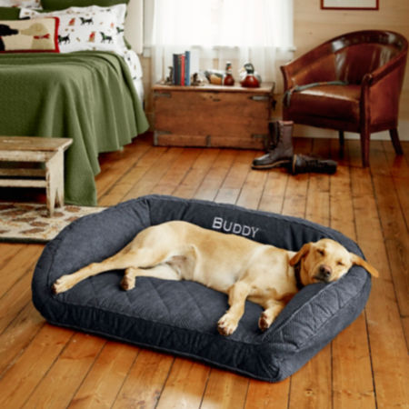 Golden lab laying on a dog bed in a bedroom
