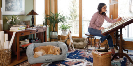Woman working at home with her dog laying on an Orvis dog bed