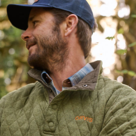 Close up of a man wearing a quilted sweatshirt in the forest.