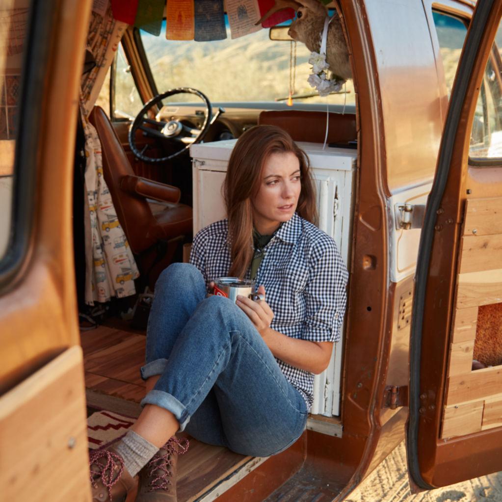 Woman drinking coffee in her van in the desert