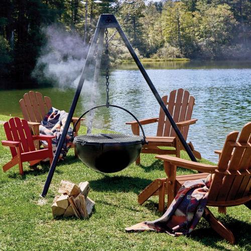 cowboy cauldron surrounded by Adirondack chairs next to a lake.
