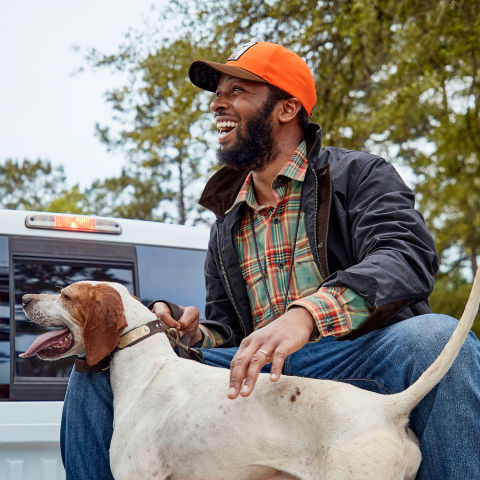 Durrell smiling with his hunting dog