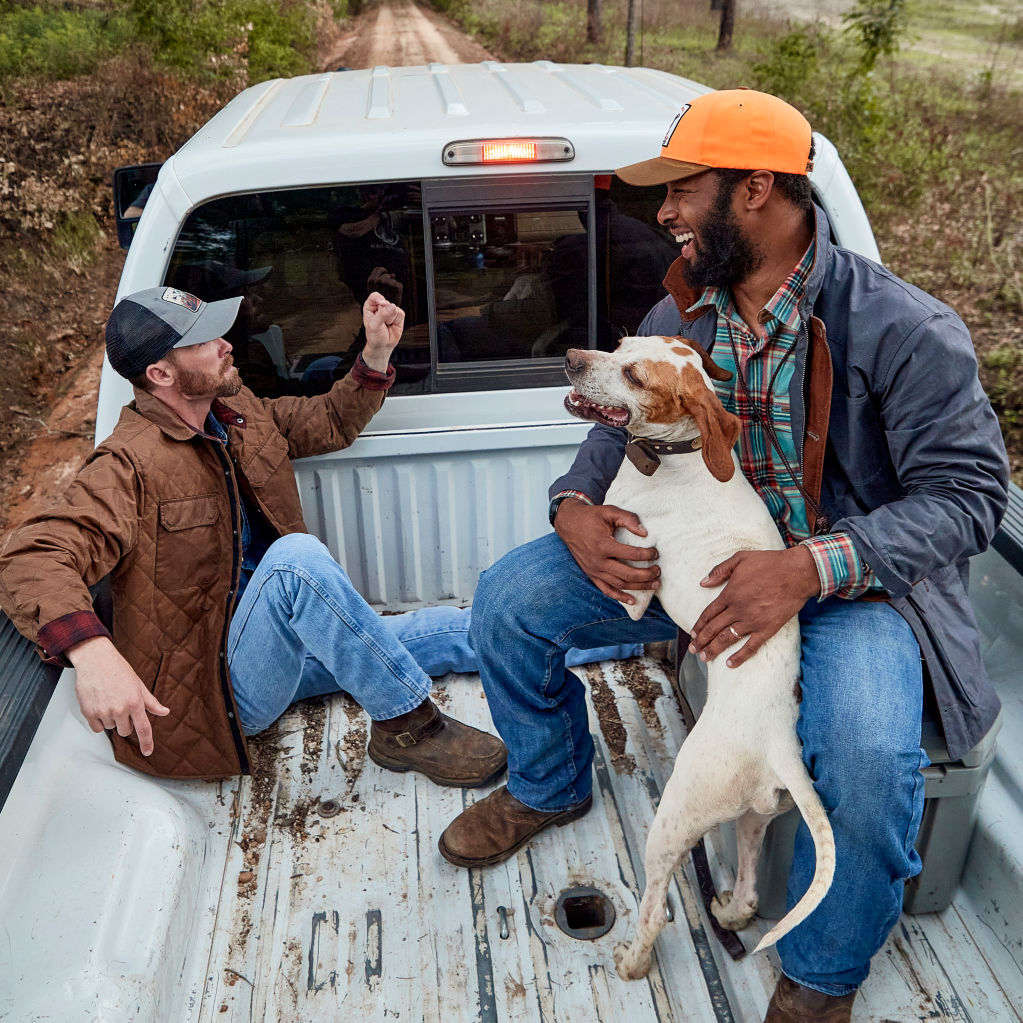Two men talking in the back of a truck with a dog