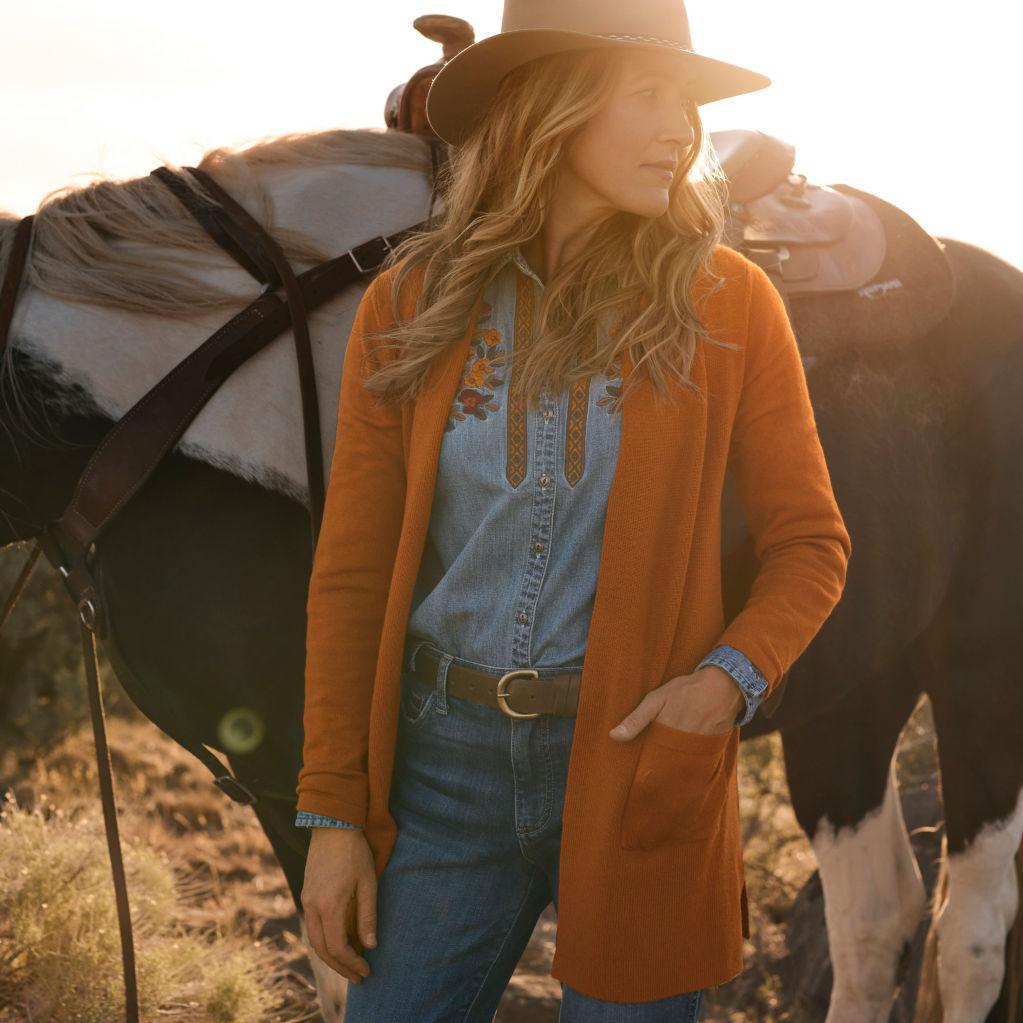 Jillian standing in front of her horse wearing orange cardigan