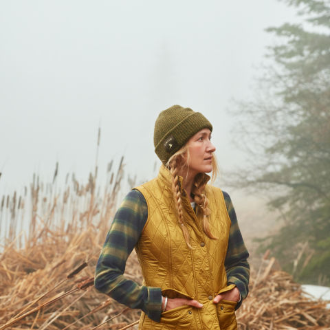 Woman wearing Lodge Flannel shirt and gold vest standing in a field