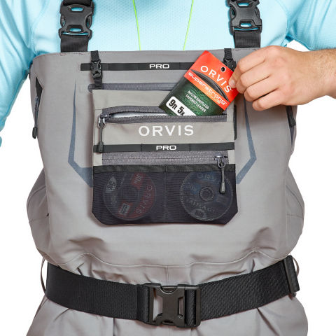 Slipping a pack of tippet into the Pro waders external storage pocket.