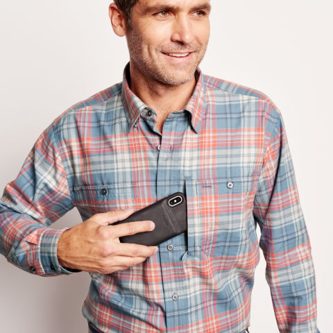Cell phone being placed in a hidden shirt pocket.