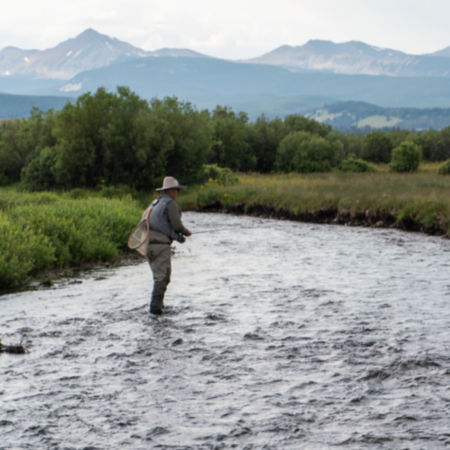 An angler casts while standing in a shallow river.
