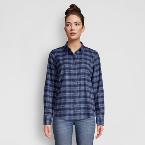 Model standing wearing a flannel shirt and jeans.