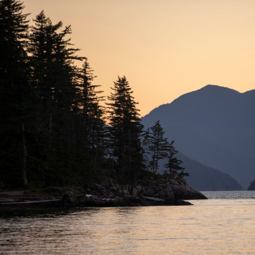 Sun setting on an Canadian river with mountains in the background