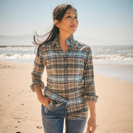 A woman, wearing a plaid shirt, stands on the beach with the ocean behind her.