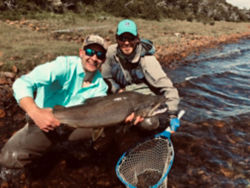 two men holding a large fish