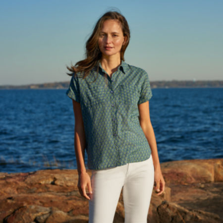 Woman standing on a rocky shore wearing new products for summer.