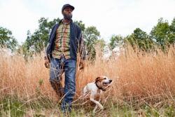 A man and dog walking through a field