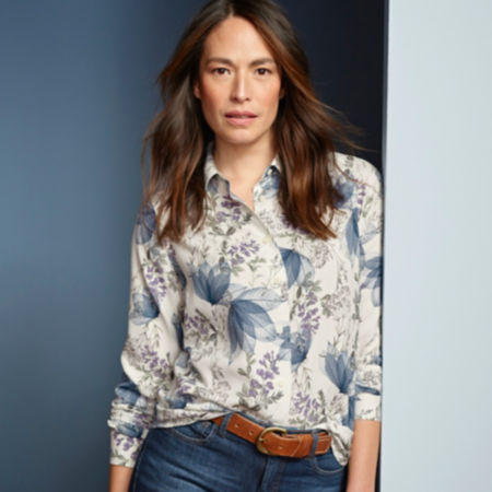 Woman smiling wearing a patterned silk button-down shirt