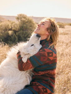 A woman hugging a fluffy white dog