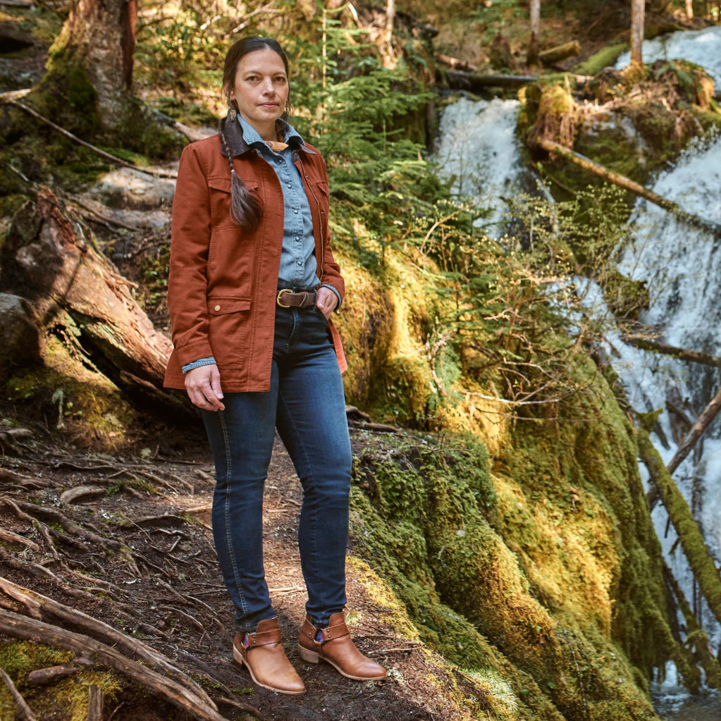 Amanda standing in the woods next to a waterfall