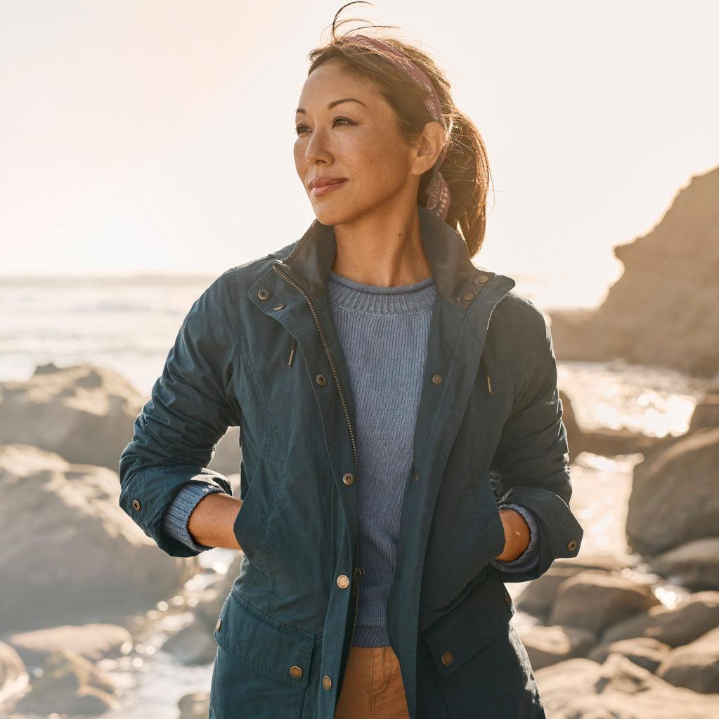 woman facing camera standing on a shoreline