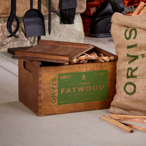 crate of fatwood kindling sitting on the floor in front of a fireplace