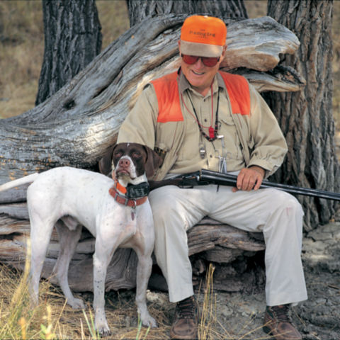 Leigh H Perkins in hunting gear, sitting on a tree stump next to a hunting dog