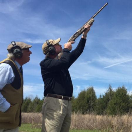 Man guiding another man shooting a shotgun in the air