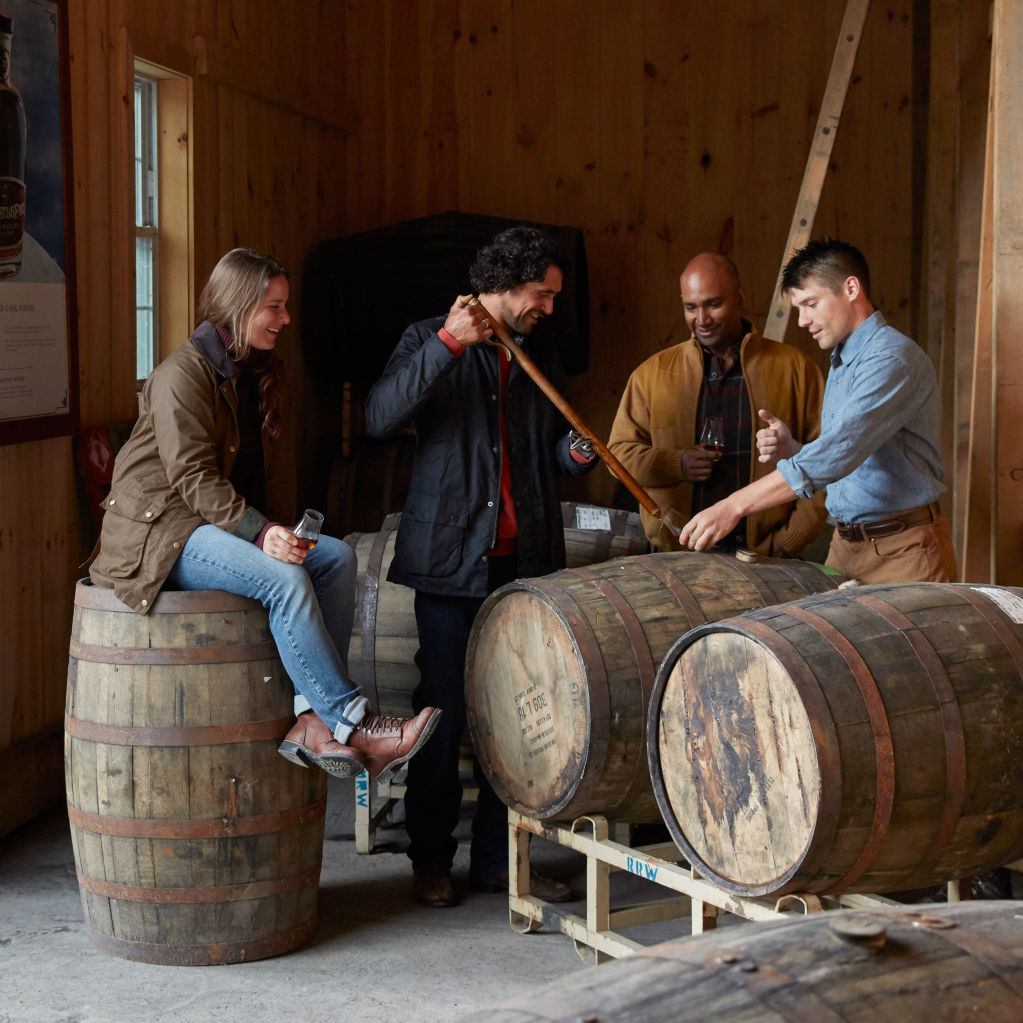 Group of people around a whiskey barrel