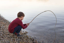 Little boy fishing with a branch