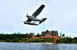 a float plane taking off of a lake with a log cabin in background