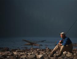 angler sitting alone on rocky shoreline
