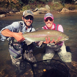 a man and a woman holding a large fish