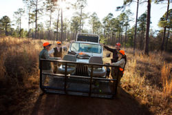 Group of hunters gathered around a Jeep