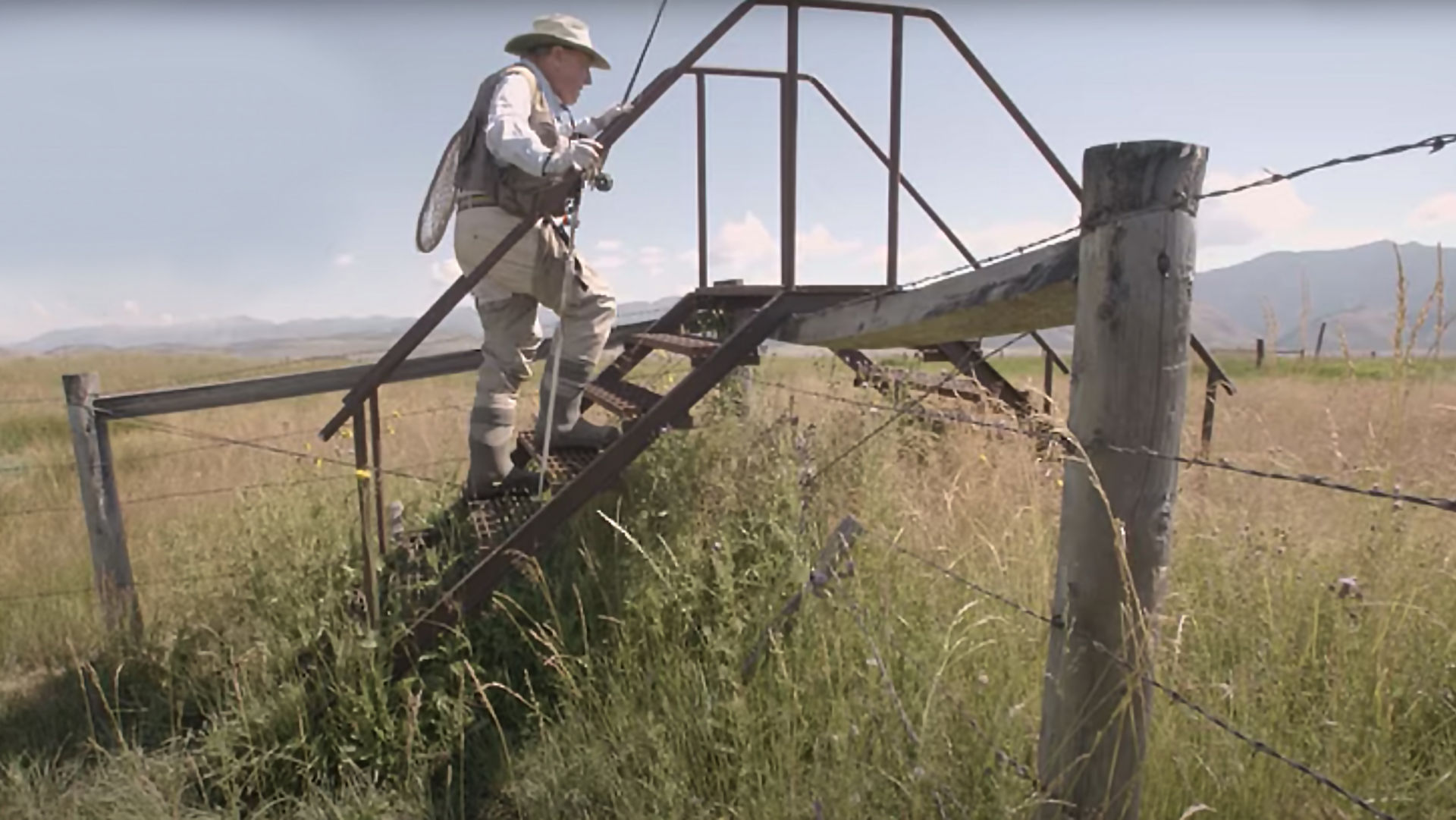 old man in fishing gear using ladder to traverse fence
